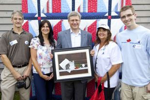 Bible Hill artist Janice Guinan presented a painting to Prime Minister Stephen Harper during an event in Forties, Lunenburg County. Guinan's family was also on hand during the presentation. From left, Dave Guinan, Janice Guinan, Prime Minister Stephen Harper